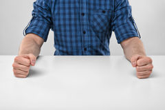 Closeup masculine fists clenched on the table. Anger sign. Nervous condition. Body language. Hand gesture. Aggression and threat. Defensive reaction Stock Images