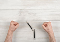 Closeup masculine fists clenched on wooden panel with broken pen Royalty Free Stock Image