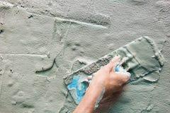Closeup mason hand fresh concrete mix with trowel Stock Photos