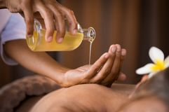 Therapist pouring massage oil at spa. Closeup of masseur hands pouring aroma oil on women back. Masseuse prepare to do oriental spa procedure for relaxing royalty free stock images