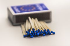 Blue matches and box. Closeup of matchbox with stack of blue headed matches in front Royalty Free Stock Photo