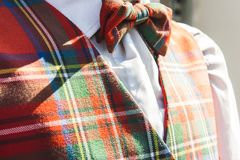 Closeup of matching tartan bowtie and waistcoat outdoors in the. Warm sunlight with a white shirt menswear clothing royalty free stock image