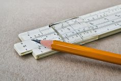 Closeup of a slide rule. Closeup of a mathematical slide rule and yellow pencil Stock Photos