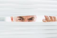 Closeup of a mature businessman peeking through blinds Stock Photos