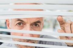 Closeup of a mature businessman peeking through blinds Stock Photography