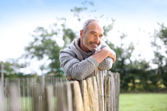 Closeup of mature man leaning on wood fence. Mature man standing by fence in countryside royalty free stock photography