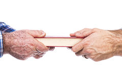 Closeup of mature man´s hand giving a book to his son Royalty Free Stock Photo