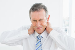 Closeup of a mature man suffering from neck pain Royalty Free Stock Images