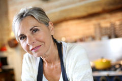 Closeup of mature woman with grey hair standing in kitchen Royalty Free Stock Photo