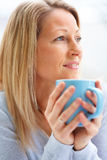 Closeup  of a mature woman holding a coffee cup Stock Images