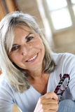 Closeup of mature woman at home with eyeglasses in hand Royalty Free Stock Images