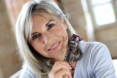 Closeup of mature woman removing eyeglasses Stock Photography