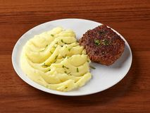 Closeup of meat cutlet and mashed potatoes. In a white plate on a wooden background royalty free stock image