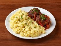 Closeup of meat cutlet with sauce and boiled pasta. In a white plate on a wooden background stock photos