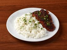 Closeup of meat cutlet or schnitzel and boiled white rice. In a white plate on a wooden background royalty free stock images