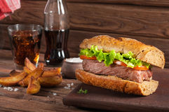 Closeup meat sandwich, potatoes and cola on wooden background stock photos