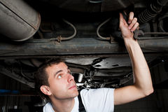 Closeup of mechanic working below car. With wrench Royalty Free Stock Images