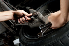 Closeup of mechanics hands working below car. With wrench Stock Photos