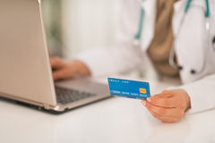 Closeup on medical doctor woman with credit card Royalty Free Stock Image