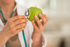 Closeup on medical doctor woman examining apple. With stethoscope Royalty Free Stock Photos