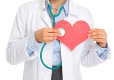 Closeup on doctor woman listening paper heart Royalty Free Stock Photo