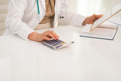 Closeup on medical doctor woman using calculator stock images