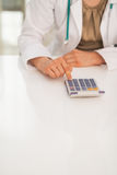 Closeup on medical doctor woman using calculator Royalty Free Stock Image