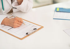 Closeup on medical doctor writing in clipboard Stock Images