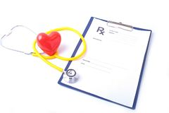 Closeup of medical stethoscope on a rx prescription, red heart isolated on white background.  Royalty Free Stock Image