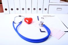 Closeup of medical stethoscope on a rx prescription, red heart isolated on white background stock photography