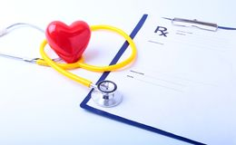 Closeup of medical stethoscope on a rx prescription, red heart on white background royalty free stock photography