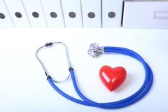 Closeup of medical stethoscope on a rx prescription, red heart on white background stock images