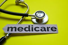 Closeup medicare with stethoscope concept inspiration on yellow background stock images