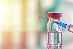 Closeup of medicine vial or flu, measles vaccine bottle with syringe and needle for immunization on vintage medical background,. Medicine and drug concept royalty free stock photography