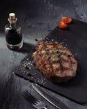 Closeup of medium rare roast beef steak. With herbs and bottle of sauce Stock Photos