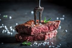 Closeup of medium rare steak with rosemary. On metal table stock image