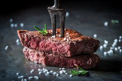 Closeup of medium rare steak with salt and herbs. On metal table royalty free stock photos