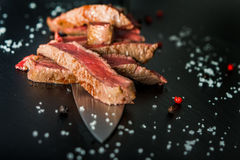 Closeup of medium rare steak slices on a knife. Medium rare steak slices on a knife on black plate, with salt flakes and peppercorns royalty free stock images