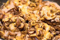 Closeup of melted cheese, mushrooms and onions on burgers Royalty Free Stock Photography