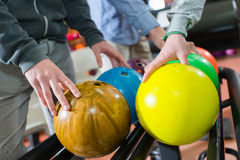 Closeup men choosing their bowling ball. Closeup of men choosing their bowling ball Stock Images