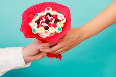 Closeup of man giving woman candy bunch flowers stock photo