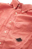 Closeup Mens Shirt Ink Stained by Leaky Pen. A closeup of a reddish shirt with a large, black ink stain on the pocket area from a leaky pen. Vertical version royalty free stock photo