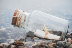 Message in a bottle on the beach. Closeup of message in a bottle on the beach royalty free stock images