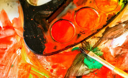 Closeup of messy, used water-color paint box and paint brush Royalty Free Stock Photo