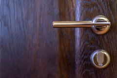 Closeup of metal bronze doorknob. Close-up of hand holding metal bronze doorknob on wooden door Royalty Free Stock Photos