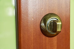 Closeup of metal bronze doorknob. Close-up of metal bronze doorknob on wooden door Stock Image