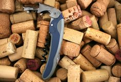 Closeup of a metal corkscrew in the midst of wooden corks stock images