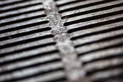 Closeup of the metal drain grate surface Royalty Free Stock Photo