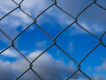 Closeup of metal chainlink fence in front of dramatic blue cloudy sky Stock Images