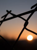Closeup of metal fence at sunrise, background blurry Stock Photos